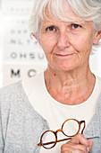 Elderly woman holding glasses