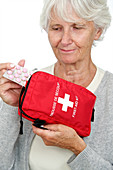 Elderly woman with first aid kit