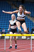 Senior female athlete clears hurdle