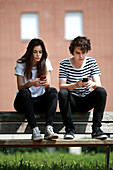Teenage couple using smart phones