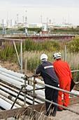 Workman inspect a pipeline
