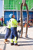 Workers next to a crane hook