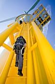 A worker climbs a turbine