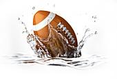 Rugby ball splashing into water,artwork