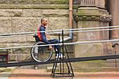 Man in wheelchair using a ramp