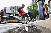 Man in wheelchair going over a curb