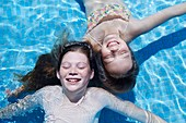 Two girls floating in water
