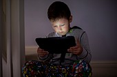 Boy using a digital tablet in the dark