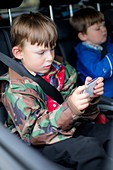 Boy in car using digital device