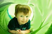 Boy in green tunnel