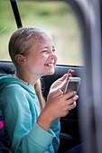 Girl using smartphone in car