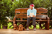 Man sitting on bench with dogs