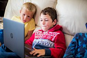 Two boys using a laptop sitting on sofa
