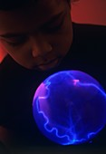 Boy watching a plasma globe