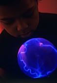 Boy watching a plasma globe
