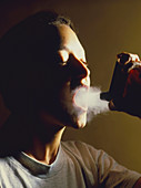 Young woman using aerosol inhaler for asthma