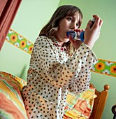 Girl with asthma uses an inhaler adaptor indoors