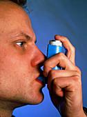 Young man using an aerosol inhaler for asthma