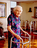 Elderly woman uses a walking frame in old age home