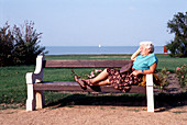 Pensioner relaxing on a bench