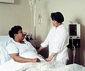 Nurse attends to a female patient on hospital ward