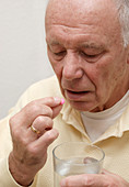 Elderly man taking medication