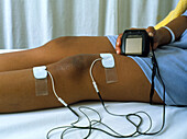 Hand operating a TENS unit for knee pain