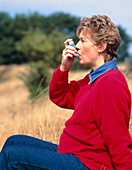 Pregnant woman using an inhaler to control asthma