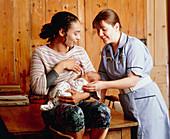 Midwife helps mother to establish breastfeeding