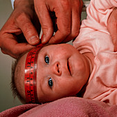 Doctor's hands measuring with tape a baby's head