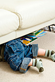 Toddler crawling beneath a sofa