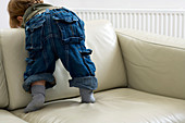 Toddler climbing on a sofa