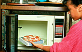 Child danger: girl places food in microwave oven