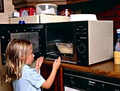 Child danger: young girl takes food from microwave