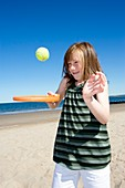 Girl playing with a bat and ball