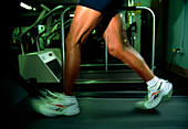 Time-exposure image of legs running on a treadmill
