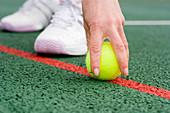 Tennis player picking up a ball