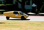 Solar powered car drives down a road