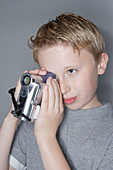 Boy using a digital camcorder
