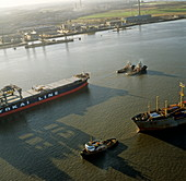 Container ship being towed by tug boats
