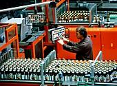 Worker on an apple juice bottling line