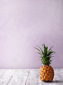 A pineapple on a grey wooden surface