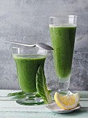 Two green smoothies garnished with chard and lemon