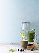 Two green smoothies garnished with parsley and celery sticks