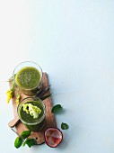 Two green smoothies garnished with golden rod and lettuce