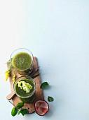 Zwei grüne Smoothies, mit Goldrute und Kopfsalat dekoriert