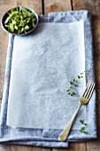Graues Küchentuch und Backpapier auf rustikalem Holztisch