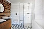 Badezimmer mit rustikaler Holzbohlenwand, Badewanne und verglastem Duschbereich