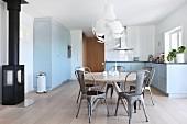 Essplatz mit grauen Retro Metallstühlen um runden Klassikertisch in blau-grauer Landhausküche