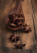 Star anise with a wooden spoon on a wooden surface
